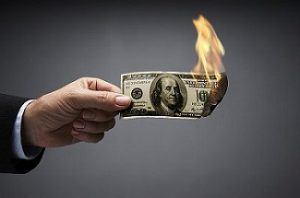 Businessman burning 100 dollar bill